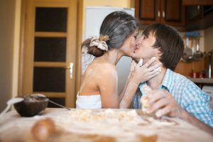 lovers kissing in kitchen covered in flour