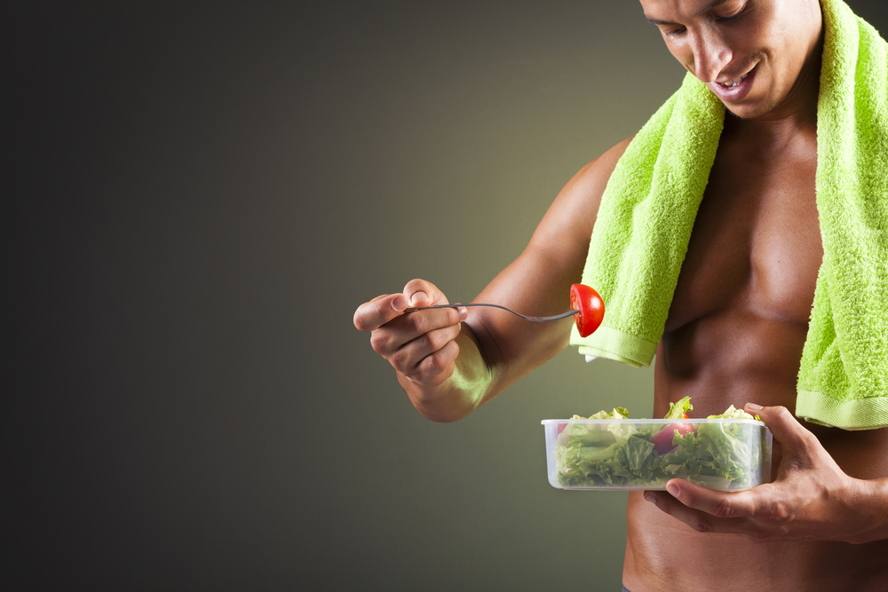 fit muscular man eats salad along