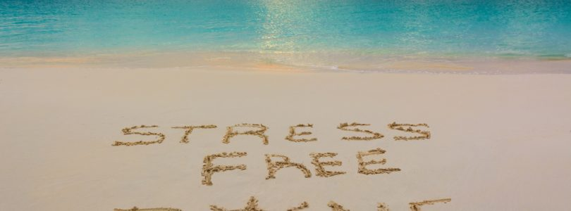 stress free zone written on sandy beach