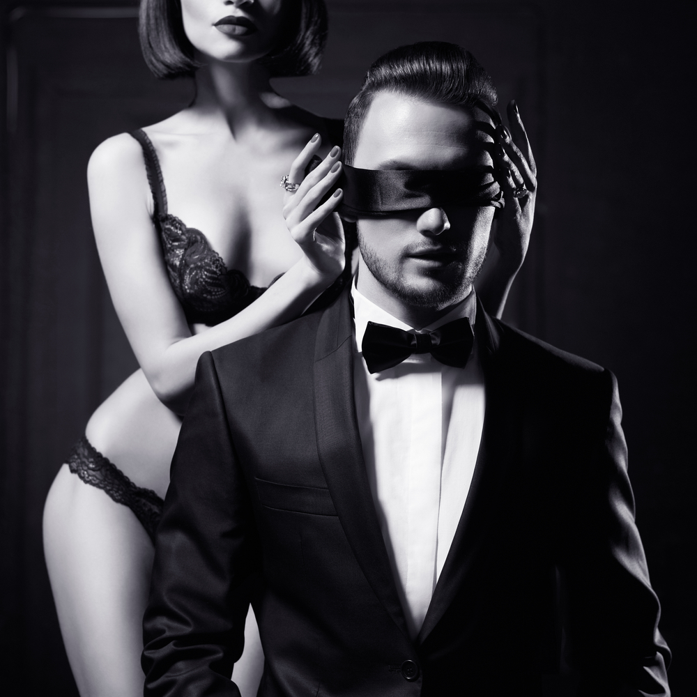 man in suit blindfolded by woman in lingerie, sexual role play