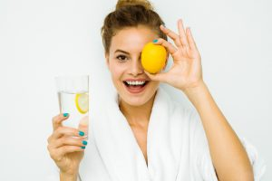 woman with vitamin C water and citrus in hand