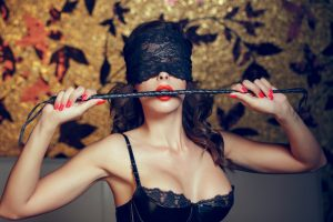 Sexy woman in blindfold bite whip with red lips, lace eye cover, bdsm