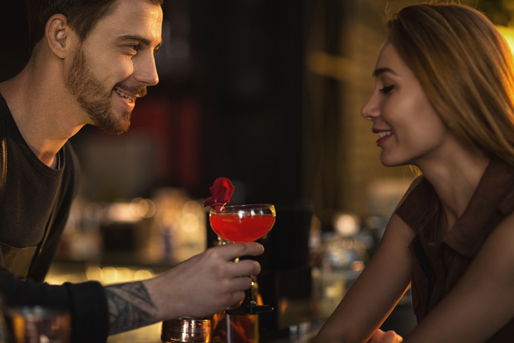 man getting woman's attention in bar is more confident