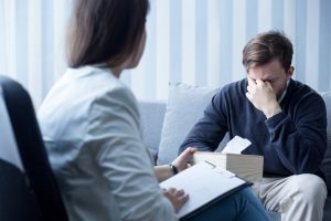 man with postpartum depression seeking treatment from therapist