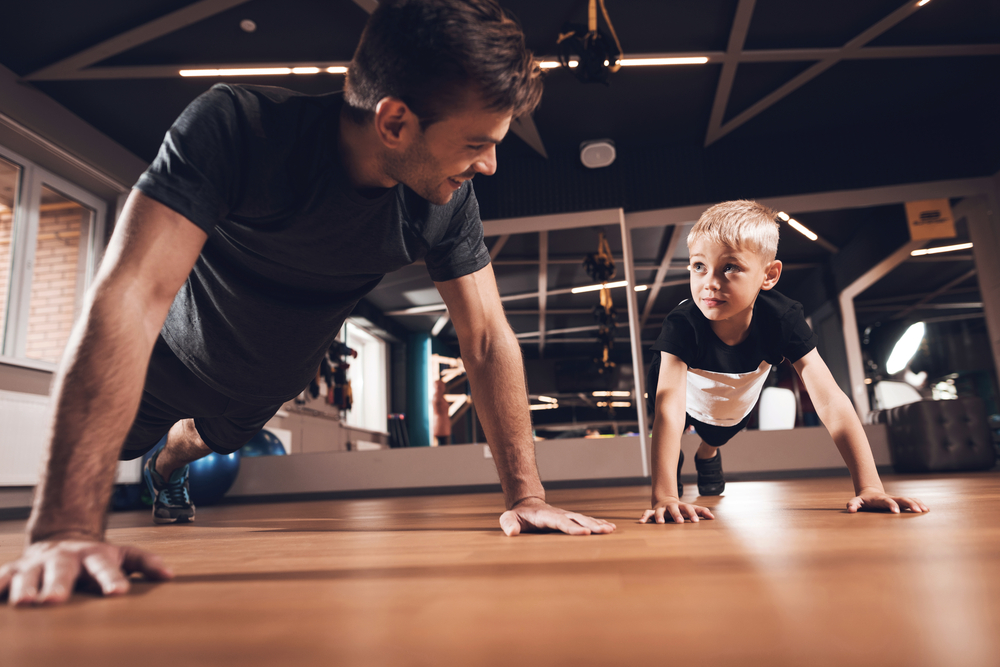 dad and his son exercising in the gym