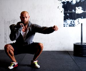 man doing squats while holding kettle bell