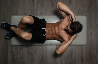 ripped guy doing floor crunches has been taking Progentra regularly