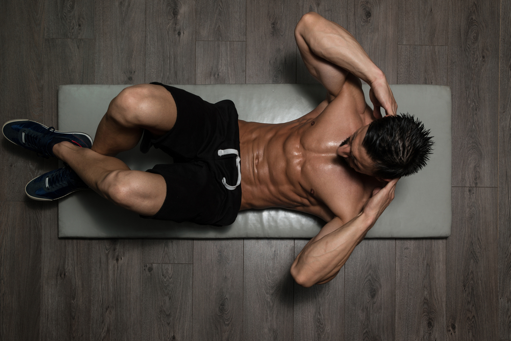 ripped guy doing floor crunches