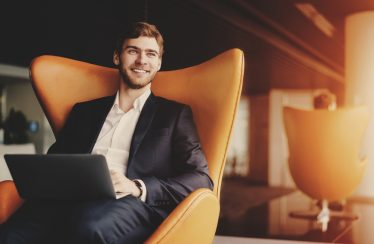 successful businessman sitting with computer on his lap
