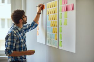 young entrepreneur writing reminders on board full of post-it notes