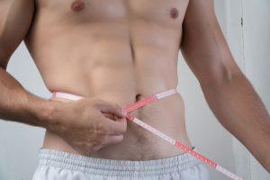 fit man measuring his waist